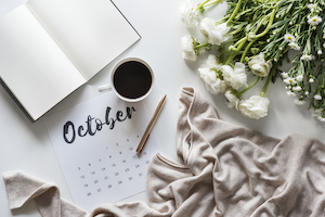 a calendar open to October, surrounded by a pen, a mug of coffee, a sweater, an open writing book and some flowers